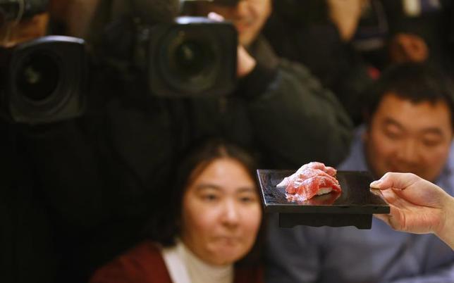 Guests look at tuna sushi made from a 222 kg (489 lbs) bluefin tuna at a sushi restaurant outside Tsukiji fish market in Tokyo January 5, 2013. REUTERS/Toru Hanai