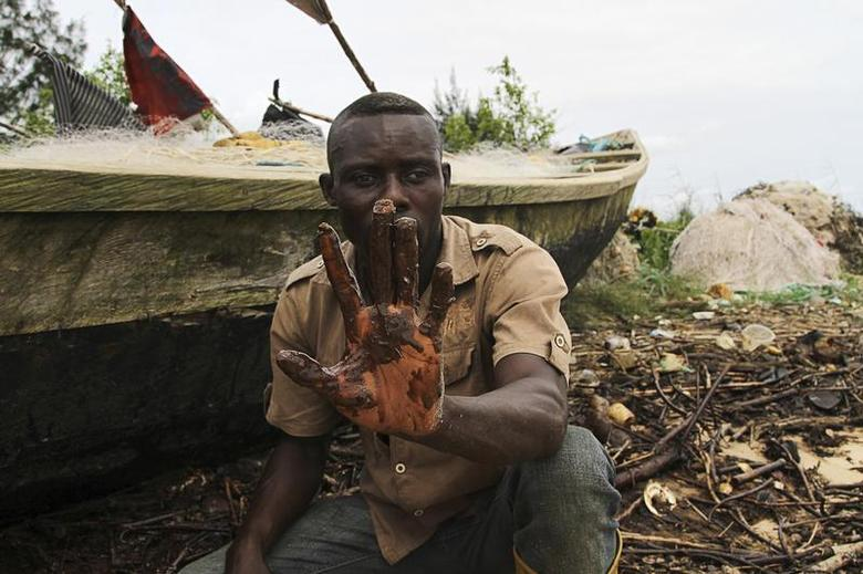 A fisherman shows oil slick on his palm, by the shore of the Niger Delta region in Brass December 2, 2013. REUTERS/Stringer
