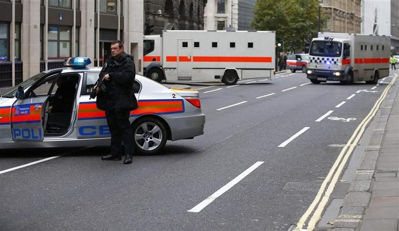 Police officers block the street while defendants under armed guard are driven into the Old Bailey in central London, December 3, 2013. The trial of two men accused of killing a soldier on a south London street continues at the Old Bailey today. REUTERS/Andrew Winning