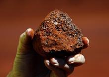 Um minerador segura um pedaço de minério de ferro em uma mina localizada na região de Pilbara, no Estado de Western Australia. A Rio Tinto planeja cortar os investimentos para 8 bilhões de dólares em 2015 ante o nível do ano passado, para reduzir dívida, no movimento mais recente de uma mineradora para reduzir gastos enquanto os preços das commodities continuam frágeis. 02/12/2013 REUTERS/David Gray