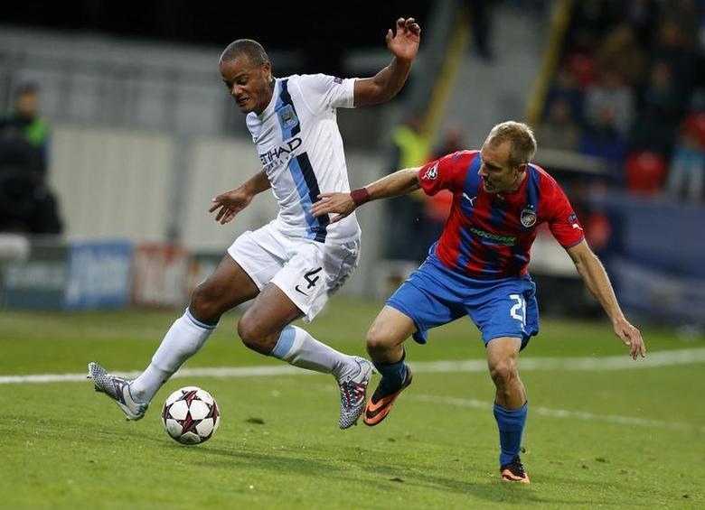 Manchester City's Vincent Kompany (L) challenges Viktoria Plzen's Daniel Kolar during their Champions League group D soccer match at the Doosan Arena in Prague, Czech Republic September 17, 2013. REUTERS/Petr Josek