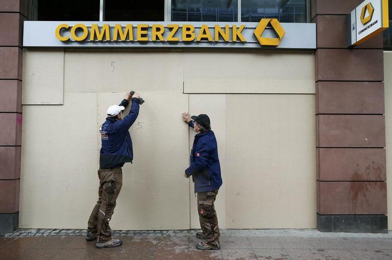 Workers install boards to protect a branch of German Commerzbank next to the headquarters of the European Central Bank (ECB) in Frankfurt May 29, 2013. REUTERS/Ralph Orlowski