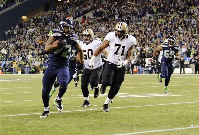 Seattle Seahawks defensive end Michael Bennett (L) runs the ball in for a touchdown after recovering the fumble by New Orleans Saints quarterback Drew Brees (not pictured) during the 1st quarter at CenturyLink Field in Seattle, Washington in this file photo from December 2, 2013. Steven Bisig