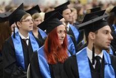 Students wearing hats listen to a speech during their graduation ceremony at the Hamburg School of Business Administration (HSBA) in Hamburg, in this September 26, 2012 file picture. REUTERS/Fabian Bimmer/Files