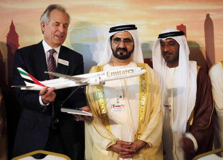 Boeing Chairman James McNerney (L) shows United Arab Emirates' Prime Minister and Ruler of Dubai Sheikh Mohammed bin Rashid al-Maktoum (2nd R) a model of the new version of its 777 long-haul jet during the Dubai Airshow November 17, 2013. REUTERS/Ahmed Jadallah