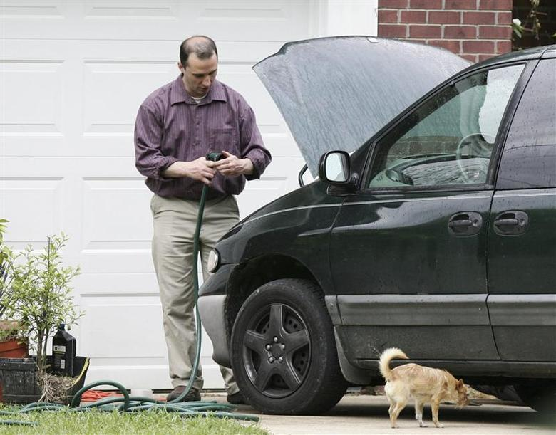Everett Dutschke works on his mini-van in his driveway in Tupelo, Mississippi, in this file photo taken April 26, 2013. REUTERS/Thomas Wells/Files