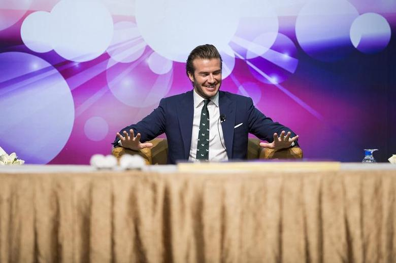 Former England soccer team captain David Beckham reacts during a promotional event at the Venetian Macao hotel in Macau November 22, 2013. REUTERS/Tyrone Siu