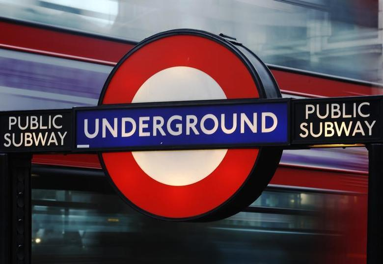 A bus passes a sign for the London Underground tube system in London January 29, 2013. REUTERS/Luke Macgregor