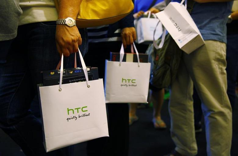 Customers hold bags containing their HTC One mobile phone purchases during the first day of public sales at Taman Anggrek Mall in Jakarta, June 8, 2013. REUTERS/Beawiharta