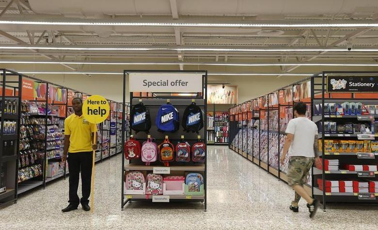 A customer service representative stands in an aisle at a Tesco Extra supermarket in Watford, north of London August 8, 2013. REUTERS/Suzanne Plunkett