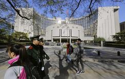 People walk past the headquarters of the People's Bank of China (PBOC), the central bank, as two paramilitary police officials patrol around it in Beijing November 20, 2013. REUTERS/Jason Lee