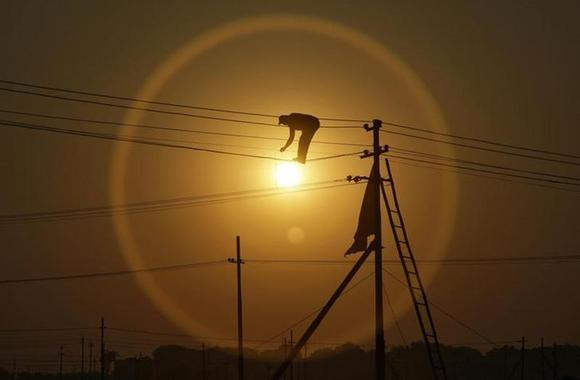 An employee from the electricity board works on newly installed overhead power cables ahead of the ''Kumbh Mela'', or Pitcher Festival, as the sun sets in Allahabad December 7, 2012. REUTERS/Jitendra Prakash/Files