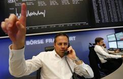 Трейдер Маттиас Прегер на фоне экрана с динамикой индекса DAX на Франкфуртской фондовой бирже 27 ноября 2013 года. Европейские фондовые рынки в основном растут после резкого снижения накануне и вслед за публикацией отчета о ВВП еврозоны. REUTERS/Kai Pfaffenbach