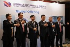 Топ-менеджеры компании China Cinda Asset Management Co Ltd позируют фотографам перед завтраком с инвесторами в Гонконге 25 ноября 2013 года. Армия частных инвесторов Гонконга намерена вложиться в крупнейшее местное IPO в этом году - Cinda Asset Management Co Ltd, уже поддержанное глобальными игроками и Пекином. REUTERS/Bobby Yip