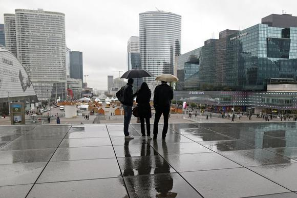 People are silhouetted as they shelter from rain under the Arche de la Defense, in the financial district west of Paris, November 8, 2013. REUTERS/Charles Platiau