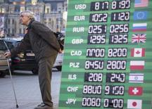 Мужчина стоит у вывески обменного пункта в Киеве 16 октября 2013. Национальный банк Украины, обещавший вмешиваться для сохранения стабильности на финансовых рынках, взволнованных политическим кризисом, второй раз за неделю объявил об интервенции долларов в поддержку снижающейся гривны. REUTERS/Gleb Garanich
