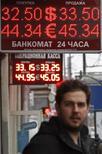 Человек проходит под табло обменного пункта в Москве 28 ноября 2013 года. Рубль подорожал в среду за счет сокращения локального спроса на валюту, сместившего баланс в сторону продавцов в условиях тонкого и низкооборотного перед важными событиями рынка. REUTERS/Maxim Shemetov