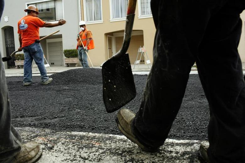 Workers spread asphalt on a street in the Cow Hollow neighborhood in San Francisco, California June 2, 2010. REUTERS/Robert Galbraith