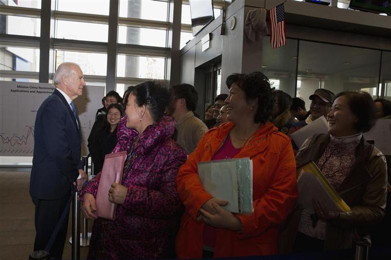 U.S. Vice President Joe Biden (L) talks to visa applicants at the U.S. Embassy Consular Section in Beijing December 4, 2013. REUTERS/Ng Han Guan/Pool