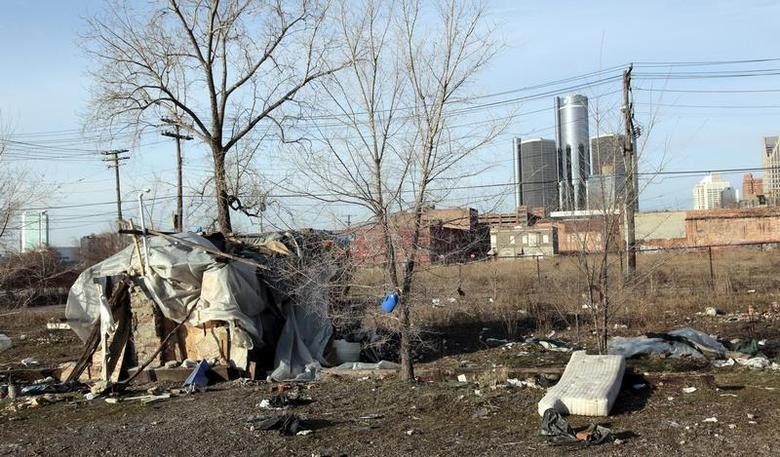 A makeshift homeless persons structure is seen, with General Motors Corp. world headquarters headquarters in the background, from an mostly abandoned warehouse district in Detroit, Michigan March 31, 2009. REUTERS/Rebecca Cook