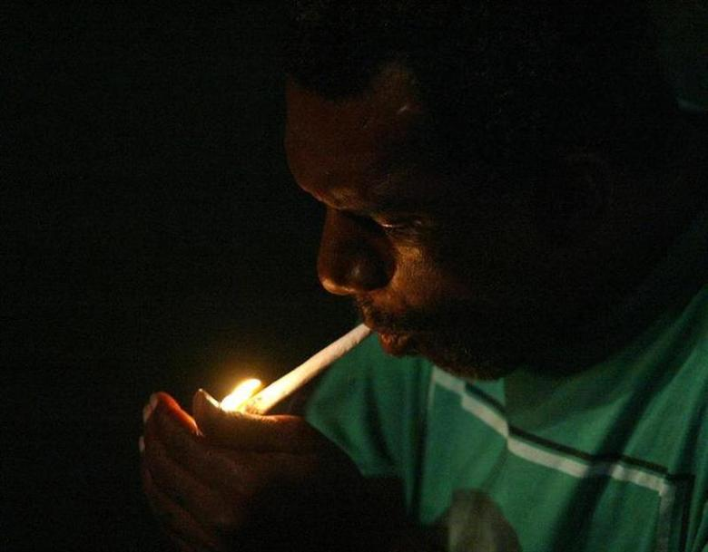 A man lights a marijuana cigarette in West Kingston, Jamaica, in a file photo. REUTERS/Andrew Winning