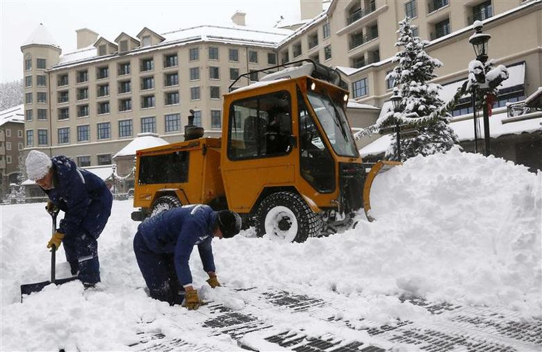 Workers clear snow off an ice skating rink in Beaver Creek, Colorado, December 4, 2013. REUTERS/Rick Wilking