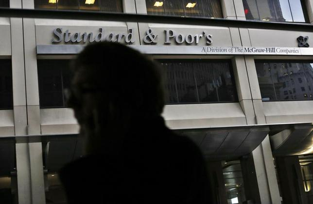 A man walks past the Standard and Poor's building in New York's financial district February 5, 2013. REUTERS/Brendan McDermid/Files