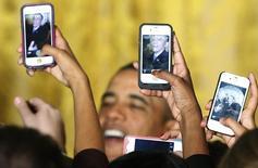 """Участницы встречи с президентом США Бараком Обамой в Белом доме фотографируют его на свои телефоны 18 марта 2013 года. На встрече с молодежью в среду Обама рассказал, что iPhone ему не положен из """"соображений безопасности"""", но он пользуется другим продуктом американской Apple - планшетом iPad. REUTERS/Jonathan Ernst"""