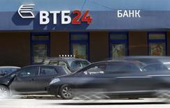 Автомобили проезжают мимо отделения банка ВТБ 24 в Москве 29 апреля 2013 года. Второй по величине госбанк РФ ВТБ в третьем квартале 2013 года снизил чистую прибыль, рассчитанную по международным стандартам, на 31 процент до 18,4 миллиарда рублей с 26,6 миллиарда рублей, сообщил банк. REUTERS/Sergei Karpukhin