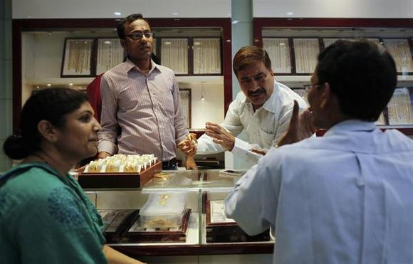 An employee shows gold bangles to a customer at jewellery showroom on the occasion of Dhanteras, a Hindu festival associated with Lakshmi, the goddess of wealth, at a market in Mumbai November 1, 2013. REUTERS/Danish Siddiqui/Files