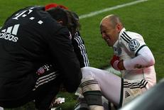 Bayern Munich's Arjen Robben reacts as medical assistants attend to his leg during the team's third round German soccer cup (DFB-Pokal) match against Augsburg in Augsburg December 4, 2013. REUTERS/Michaela Rehle