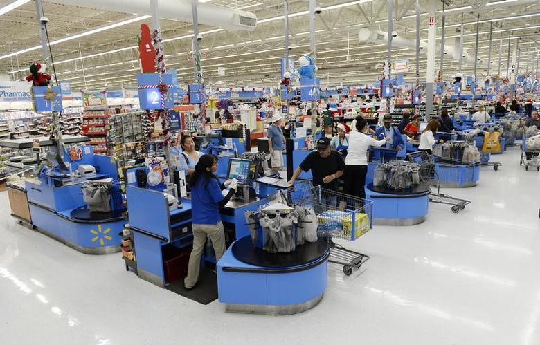 Cashiers work at the checkout lanes of a Walmart store in the Porter Ranch section of Los Angeles November 26, 2013. REUTERS/Kevork Djansezian