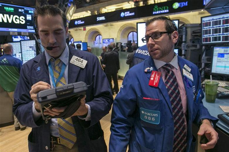 Specialist trader Michael Pistillo (R) gives a price to trader Greg Rowe on the floor of the New York Stock Exchange December 3, 2013. REUTERS/Brendan McDermid