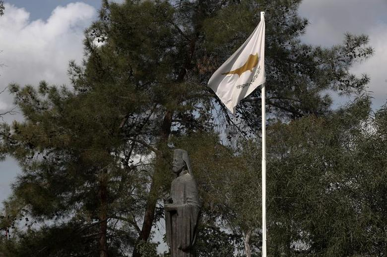 A Cypriot flag flutters over the statue of the first President of Cyprus Archbishop Makarios at the presidential palace in Nicosia February 21, 2013. REUTERS/Yorgos Karahalis