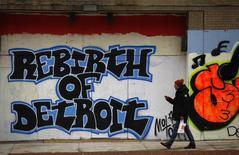 """Um homem passa em frente a um grafite em Detroit, com os dizeres """"Renascimento de Detroit"""". A economia dos Estados Unidos cresceu mais rápido do que o inicialmente estimado no terceiro trimestre, com os empresários agressivamente acumulando estoques, mas a demanda doméstica permaneceu lenta. 03/12/2013 REUTERS/Joshua Lott"""