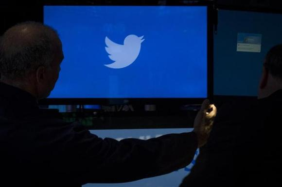 An employee adjusts a screen that displays the Twitter logo ahead of the company's IPO on the floor of the New York Stock Exchange, November 6, 2013. REUTERS/Brendan McDermid/Files