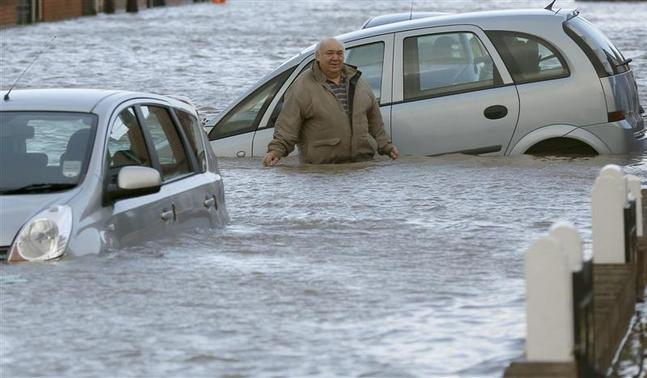 A man stands up to his waist in flood water in a residential street in Rhyl, north Wales December 5, 2013. REUTERS-Phil Noble