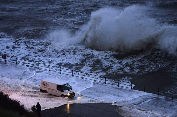A van drives through seawater washed onto the promenade of the north bay in Scarborough, northern England December 5, 2013. REUTERS-Nigel Roddis