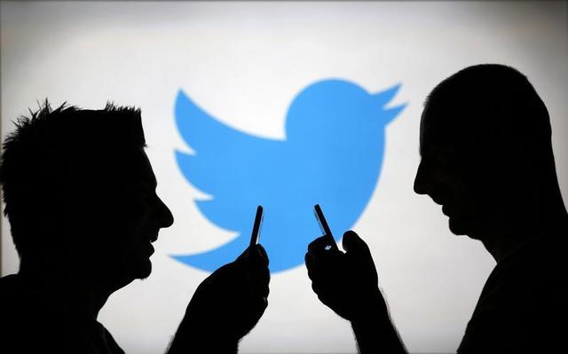 Men are silhouetted against a video screen with a Twitter logo as he poses with a Samsung S4 smartphone in this photo illustration taken in the central Bosnian town of Zenica, August 14, 2013. REUTERS/Dado Ruvic