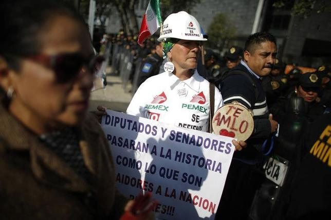 A demonstrator holds a placard while arriving to a protest against the energy reform outside the Senate building in Mexico City December 4, 2013. The placard reads: 'Lawmakers and Senators will pass in history as traitors to the nation'. REUTERS/Tomas Bravo