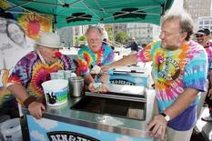 "As iconic 1960's activist Wavy Gravy (L) looks on, Ben & Jerry's Ice Cream co-founders Ben Cohen (C) and Jerry Greenfield serve the first scoop of the resurrected Ben & Jerry's flavor ""Wavy Gravy"" at an event in downtown San Francisco August 24, 2005. REUTERS/Lou Dematteis"