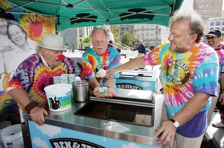 As iconic 1960's activist Wavy Gravy (L) looks on, Ben & Jerry's Ice Cream co-founders Ben Cohen (C) and Jerry Greenfield serve the first scoop of the resurrected Ben & Jerry's flavor ''Wavy Gravy'' at an event in downtown San Francisco August 24, 2005. REUTERS/Lou Dematteis