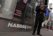 A man stands next to the Nasdaq MarketSite in New York, August 23, 2013. REUTERS/Brendan McDermid