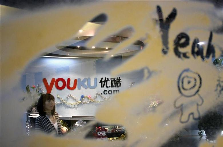 An employee is seen through a glass wall as she walks past the logo of Youku.com above the reception desk at the company's headquarters in Beijing, in this December 9, 2010 file photo. REUTERS/Soo Hoo Zheyang/Files