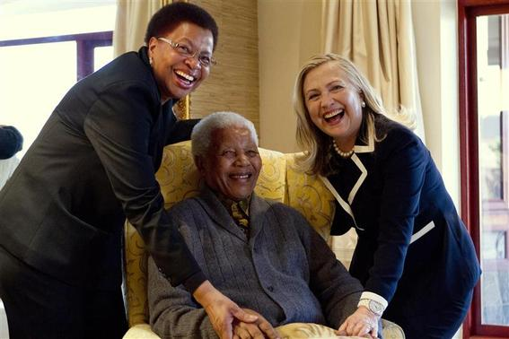 U.S. Secretary of State Hillary Clinton (R) poses for a photograph with Nelson Mandela, 94, former president of South Africa, and his wife Graca Machel at his home in Qunu in this August 6, 2012 file photo. REUTERS-Jacquelyn Martin-Pool-Files