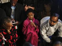 People listen to a radio as South African President Jacob Zuma announces the death of former South African President Nelson Mandela in Houghton, December 5, 2013. REUTERS/Siphiwe Sibeko