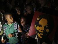 Boys look at a poster of former South African President Nelson Mandela as they gather outside Mandela's house after news of his death in Houghton, December 6, 2013. REUTERS/Siphiwe Sibeko