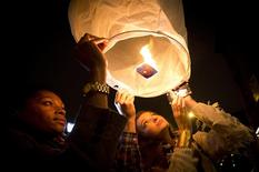 People release paper lanterns after lighting them outside Madiba, a restaurant named in honor of former South African President Nelson Mandela, in the Brooklyn borough of New York December 5, 2013. REUTERS/Carlo Allegri