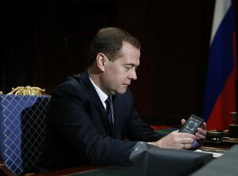 Russia's Prime Minister Dmitry Medvedev holds a YotaPhone smartphone during a meeting with Sergei Chemezov, CEO of Rostec State Corporation, at the Gorki residence outside Moscow, December 4, 2013. REUTERS/Dmitry Astakhov/RIA Novosti/Pool