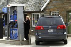 Женщина заправляет автомобиль на АЗС Exxon в Вашингтоне 2 марта 2012 года. Цены на нефть Brent растут накануне публикации отчета о занятости США и на фоне сокращения добычи нефти в Европе и США из-за плохой погоды. REUTERS/Gary Cameron
